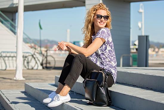 blonde girl in black pants and print top wearing white grasshoppers janey slip on canvas shoes lifestyle image sitting on boardwalk beach area Your Guide To: Top Womens Canvas Picks For Spring '19
