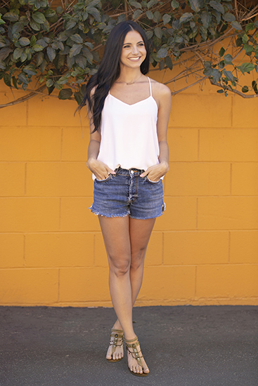brunette girl in white tank and jean shorts wearing beaded boho jellypop cava sandal