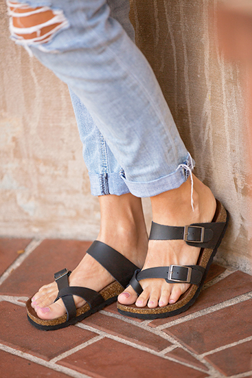 girl in ripped jeans wearing white mountain gracie black footbed sandal