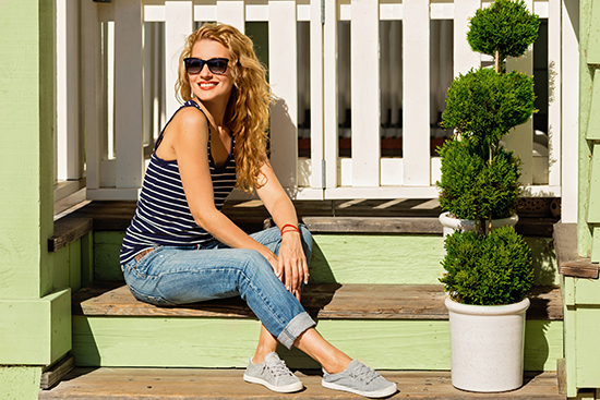 blonde woman in navy striped tank top and boyfriend blue jeans sitting on porch smiling with gray shoes
