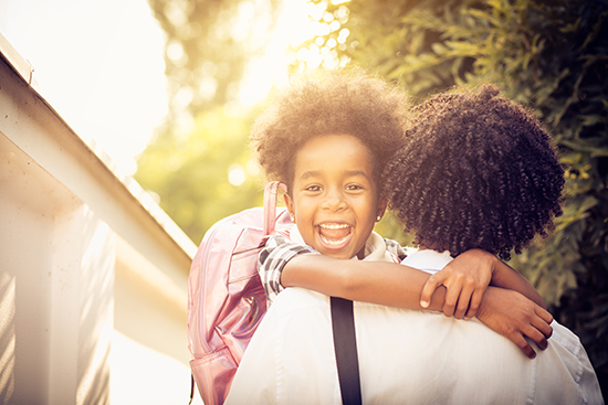 back-to-school african american girl smiling wearing a backpack with arms around her parent's shoulders